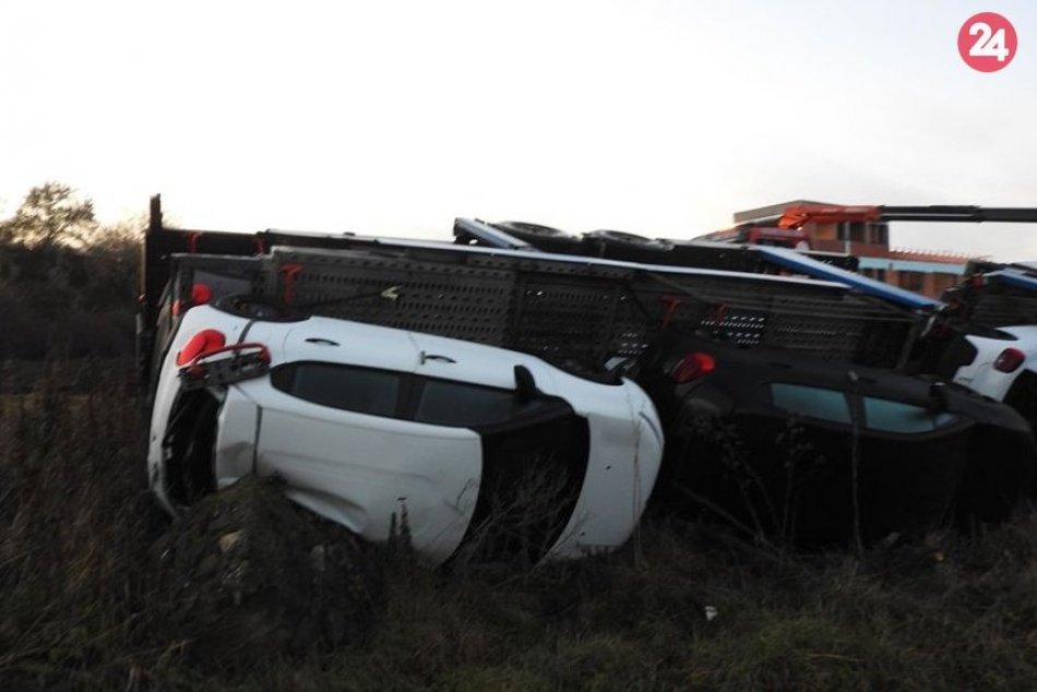 Kamión naložený autami skončil mimo cesty